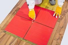 Il lavoratore livella le mattonelle degli incroci applicate sul vecchio reinforc di legno del pavimento Immagine Stock Libera da Diritti