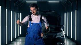 Il lavoratore maschio del garage sta ballando con gli strumenti e una lavagna per appunti in sue mani video d archivio