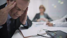 Il lavoratore maschio fa l'attacco di emicrania causare dallo sforzo e dall'esaurimento nel luogo di lavoro video d archivio