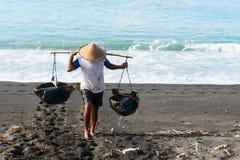Produzione di sale tradizionale del mare sulla sabbia nera vulcanica, Bali immagini stock