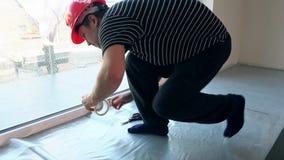 Il lavoratore maschio pone la pellicola di polietilene sul pavimento stock footage