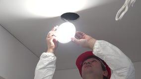 Il lavoratore maschio professionista installa il risparmio energetico principale per attaccare il foro del soffitto video d archivio