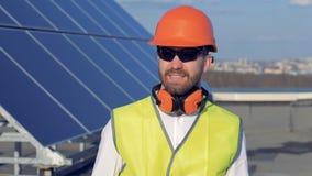 Il lavoratore maschio si gira verso la macchina fotografica ed i sorrisi, mentre sta sul tetto vicino ai pannelli del sole 4K video d archivio