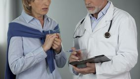 Il lavoratore medico che parla con donna che sta ottenendo ha colpito alle notizie, grandi spese archivi video