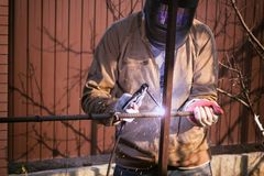 Il lavoratore in metallo di saldature della maschera protettiva con una saldatrice fotografia stock libera da diritti