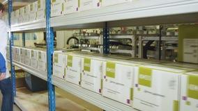 Il lavoratore mette la scatola con il sensore di moto sullo scaffale di stoccaggio video d archivio