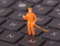 Il lavoratore miniatura sta pulendo una tastiera Immagini Stock