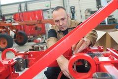 Il lavoratore monta i trattori alla fabbrica di macchine e dei trattori Fotografia Stock Libera da Diritti