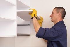 Il lavoratore monta la mobilia nella cucina Immagini Stock Libere da Diritti