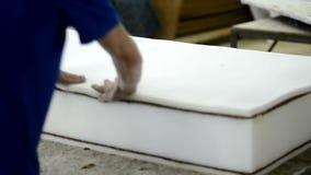 Il lavoratore nella fabbrica del materasso riguarda lo strato di base della noce di cocco di colla sul primo piano della fabbrica archivi video