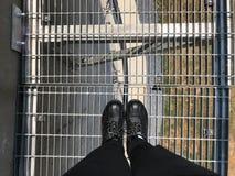 Il lavoratore o l'ingegnere con le scarpe di sicurezza sta sulla griglia del metallo su ciao Immagini Stock Libere da Diritti