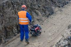 Il lavoratore-ospite sta costruendo una terra della pietra della sabbia della fossa immagine stock
