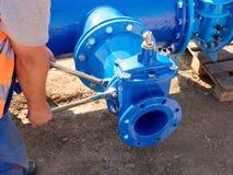 Il lavoratore passa i dadi d'avvitamento sulla nuova conduttura dell'acqua dell'anello a D Immagini Stock