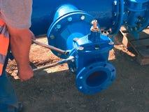 Il lavoratore passa i dadi d'avvitamento sulla nuova conduttura dell'acqua dell'anello a D Fotografia Stock