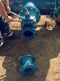 Il lavoratore passa i dadi d'avvitamento sulla nuova conduttura dell'acqua dell'anello a D Fotografie Stock Libere da Diritti
