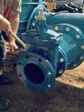 Il lavoratore passa i dadi d'avvitamento sulla nuova conduttura dell'acqua dell'anello a D Immagini Stock Libere da Diritti