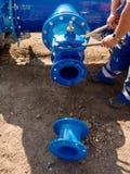 Il lavoratore passa i dadi d'avvitamento sulla nuova conduttura dell'acqua dell'anello a D Immagine Stock