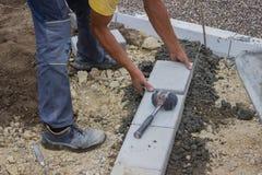 Il lavoratore pone i bordi concreti di nuovo marciapiede Immagini Stock Libere da Diritti