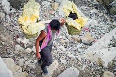Il lavoratore porta lo zolfo dentro il vulcano di Ijen del cratere, Indonesia Immagine Stock Libera da Diritti