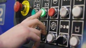 Il lavoratore preme il bottone sul pannello di controllo in primo piano dell'officina video d archivio