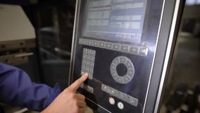 Il lavoratore preme i bottoni del pannello della macchina utensile con controllo programmato numerico L'ingegnere configura la a archivi video