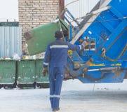 Il lavoratore a raccolta dei rifiuti, caricante barrels in un bidone della spazzatura Fotografia Stock