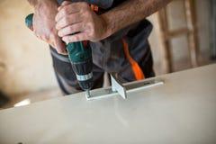 Il lavoratore ripara la porta in un'officina del ` s del carpentiere Immagini Stock Libere da Diritti