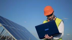 Il lavoratore scrive sul suo computer portatile, stante accanto ai pannelli del sole sulla costruzione 4K archivi video