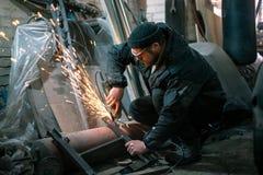 Il lavoratore sega l'acciaio negli occhiali di protezione immagini stock libere da diritti