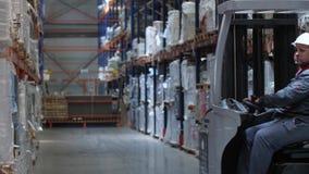 Il lavoratore si muove su una macchina di sollevamento attraverso un magazzino logistico 4K Mo lento archivi video
