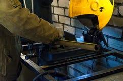 Il lavoratore si tiene per mano il tubo del metall per tagliarlo sulla macchina Contro lo sfondo dei mattoni bianchi fotografia stock