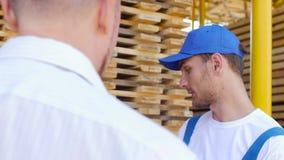 Il lavoratore, sorride e dice il compratore circa i tipi differenti di legno stock footage