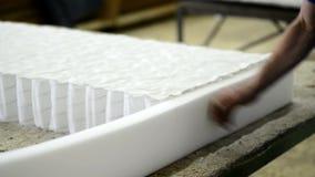 Il lavoratore spruzza la colla materiale per il materasso di produzione in fabbrica all'interno ed ha tagliato il materiale in ec archivi video