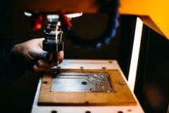 Il lavoratore sta cambiando lo strumento del trapano della taglierina in fresatrice di CNC Immagine Stock Libera da Diritti