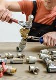 Il lavoratore sta collegando gli elementi dell'impianto idraulico immagine stock libera da diritti