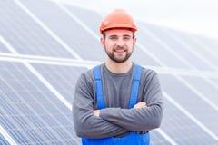 Il lavoratore sta con le sue armi attraversate contro lo sfondo dei pannelli solari Immagini Stock Libere da Diritti
