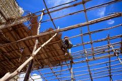 Il lavoratore sta coprendo con le foglie Casa di legno della struttura con cielo blu Fotografia Stock