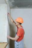 Il lavoratore sta installando un angolo di alluminio perforato Fotografia Stock