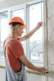 Il lavoratore sta installando un angolo di alluminio perforato Fotografie Stock Libere da Diritti