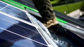 Il lavoratore sta lavando i pannelli solari sul tetto video d archivio