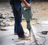 Il lavoratore sta perforando il pavimento di calcestruzzo Fotografie Stock