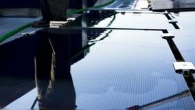 Il lavoratore sta pulendo i pannelli solari stock footage