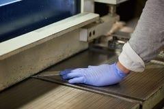 Il lavoratore sta spingendo una lamina di metallo Fotografia Stock
