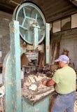 Il lavoratore taglia la legna da ardere con la sega a nastro immagini stock libere da diritti