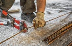 Il lavoratore taglia le barre d'acciaio con la trinciatrice per bulloni Fotografie Stock