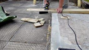 Il lavoratore taglia le barre di legno facendo uso di una sega circolare video d archivio