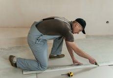 Il lavoratore taglia un pezzo di muro a secco Immagine Stock