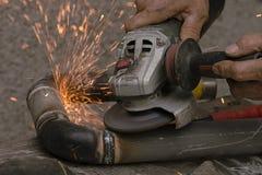 Il lavoratore taglia un tubo del metallo per mezzo dello strumento abrasivo Immagini Stock
