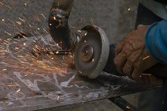 Il lavoratore taglia un tubo del metallo per mezzo dello strumento abrasivo Fotografia Stock
