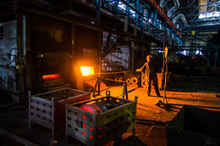 Il lavoratore tira il pezzo in lavorazione dal forno Fotografia Stock Libera da Diritti
